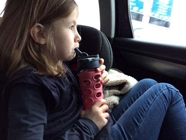 Meisje drinkt uit glazen waterfles