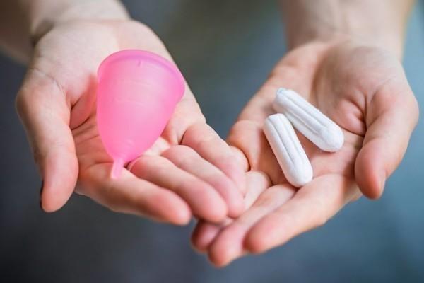 Menstruatie cup en tampons in handen